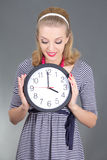 Dreaming pinup girl in striped dress with clock over grey Royalty Free Stock Photography