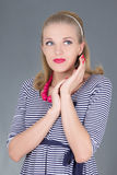 Dreaming pinup girl in striped dress posing Stock Photo