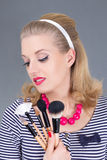 Dreaming pinup woman with make up brushes Royalty Free Stock Photography