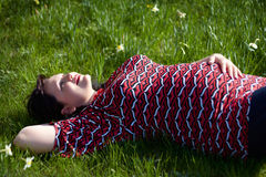 Dreaming pregnant girl lies on a grass. In park Stock Images