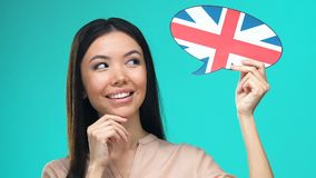 Dreaming pretty female holding English speech bubble, fluent foreign language. Stock footage stock video