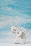 Dreaming or sad white angel on blue heaven background for a cond. Olence or christening card Royalty Free Stock Photo