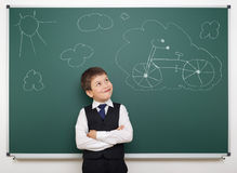 Dreaming school boy with painted bicycle. On board Royalty Free Stock Photos