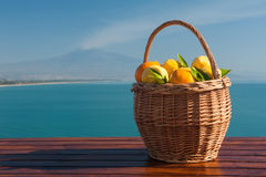 Dreaming of Sicily. Wicker basket full of oranges and lemons on a wooden table with blue sea and mount Etna in the background Stock Photography