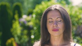 Dreaming sleeping or meditating woman outdoors in summer, eyes closed beauty stock footage