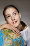 Dreaming smiling girl with blue globe Stock Photo