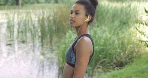 Dreaming sportswoman posing on lakeside. Side view of young ethnic woman in sportswear using headphones and posing on background of lakeside in park looking stock footage