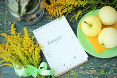 Dreaming theme, contrast of green and yellow color: apples, bunch of wild flowers, notebook on rough wooden table Stock Photos