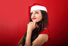 Dreaming thinking woman in santa claus christmas costume looking. Up on red background with empty copy space Stock Images