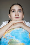Dreaming thoughtful girl with blue round globe Royalty Free Stock Images
