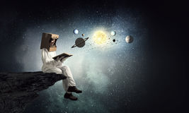 Dreaming to explore space . Mixed media. Young woman with carton box on head imagine she is astronaut Stock Photos