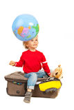 Dreaming to vacation. Child dreaming with open eyes and looking at world globe in motion and sitting on luggage against white background Stock Image