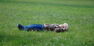 Dreaming toddler. Lying toddler on grass Stock Photography
