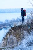 Dreaming traveler with a backpack is standing on a hill by the r Royalty Free Stock Photos