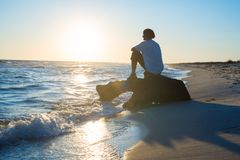 Dreaming traveler sits on a snag in the surf. And admires the sea during the sunset. Amazing adventure on the seashore. Back view, back light Royalty Free Stock Photos