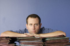 Dreaming of the weekend. Man with head in hands, dreaming of the weekend with piles of files in front of him Stock Photos