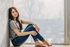 Dreaming by the window. Beautiful girl is dreaming by the window Royalty Free Stock Image