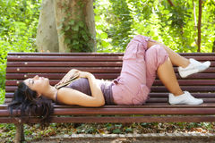 Dreaming woman. Beautiful woman dreaming after reading in a park bench stock images