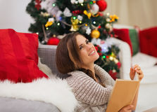 Dreaming woman with book near Christmas tree Stock Photos