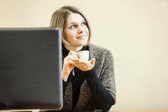 Dreaming woman with coffee cup is behind computer monitor Stock Photos