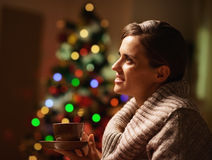 Dreaming woman with cup of beverage in front of christmas tree Stock Images