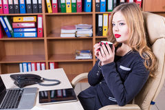 Dreaming woman with cup of coffee in the office. Dreaming woman with cup of tea in the office Stock Images