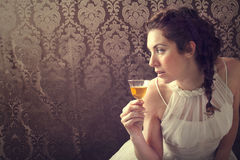 Dreaming woman drinks a glass of excellent Scotch whisky. In dining room Stock Photos