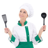 Dreaming woman in green chef uniform with kitchen tools isolated Stock Images