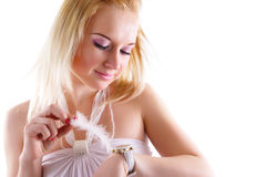 Dreaming woman looking at watch. Glamour blonde girl in white dress with feather in right hand Stock Image