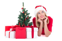 Dreaming woman lying down with christmas tree and gifts isolated. On white background Stock Image