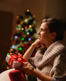 Dreaming woman sitting chair with Christmas gift Stock Images