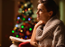 Dreaming woman sitting chair and reading book Royalty Free Stock Photos