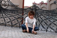 Dreaming woman sitting down outside. In front of some winged gates Stock Photos
