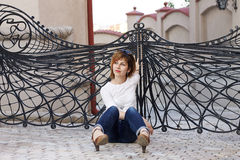 Dreaming woman sitting down outside. In front of some winged gates Stock Photo