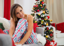Dreaming woman sitting on sofa near Christmas tree Royalty Free Stock Image