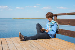 Dreaming woman is sitting on a wooden pier with tablet Royalty Free Stock Images