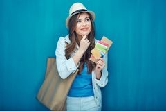 Dreaming woman traveler holding passport with ticket. Thinking woman traveler holding passport with ticket. Blue back Royalty Free Stock Photography