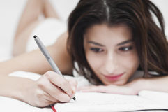 Dreaming woman writing on a notebook. Melancholic and dreaming woman writing on a notebook in the morning focused on the pen Royalty Free Stock Image