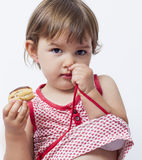 Dreaming 2 year-old child with appetite for chocolate pastry Stock Images