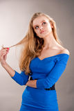 Dreaming young blonde girl touching hair. Isolated over gray stock image