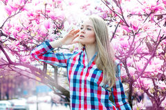 Dreaming young blonde woman looking away with flowers Royalty Free Stock Images