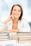 Dreaming young businesswoman with many books Royalty Free Stock Photo