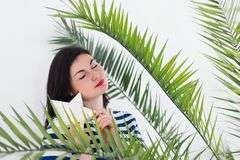 Dreaming young caucasian woman in stripped vest with white LED glowing star and green palm leaves. Summer fashion concept royalty free stock images
