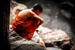 Dreaming young Monk. A young Buddhist monk sits aloof, dreaming to himself, Phnom Kulen national park, Cambodia royalty free stock image