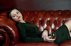 Dreaming young woman with a glass of brandy Royalty Free Stock Photo