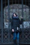 Dreaming young woman posing near a vintage iron gate Stock Photos
