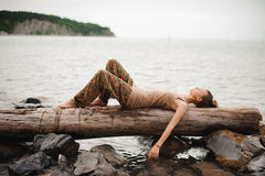Dreaming young woman is lying on the log at the water Stock Photos