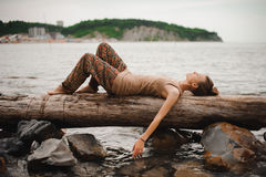 Dreaming young woman is lying on the log at the water Royalty Free Stock Image