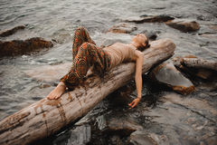 Dreaming young woman is lying on the log at the water Stock Photo