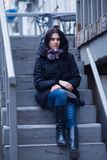 Dreaming young woman sits on a staircase of a street cafe Stock Photography